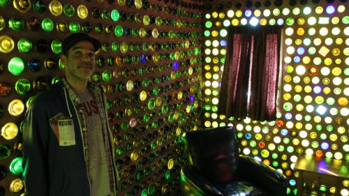 Standing inside a house made with glass bottles.